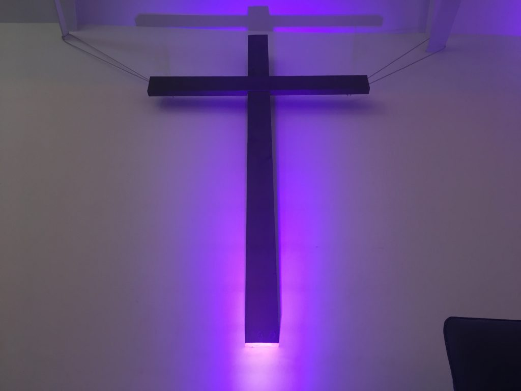 Illuminated wooden cross on a wall